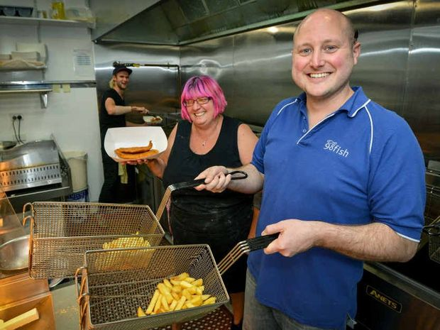 THINGS ARE COOKING: Business is flat out at 98 Fish shop, Forest Glen, proof of a retail spending boom is gathering pace. Owner Tony Roberts (front) cooks up a storm with staff Bronnie and Jordan.