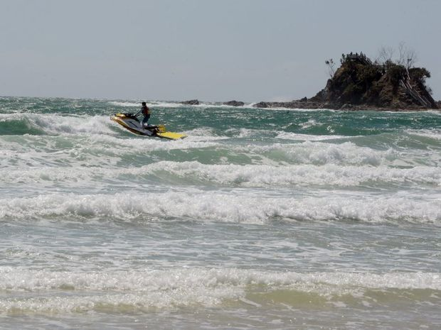 Jetskis patrol the beach on jetski in rough conditions at Clarkes Beach, Byron Bay the day after a fatal shark attack.