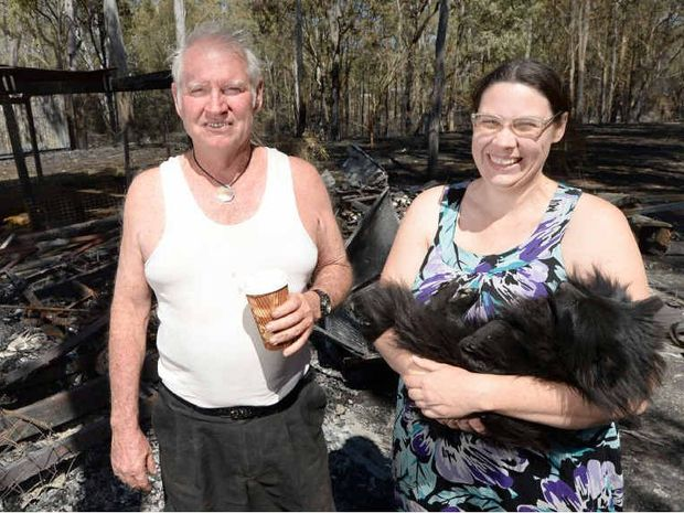 THANKFUL: Despite losing a caravan and the contents of a shipping container to fire, Ross Allan and his daughter Aleisa are happy they did not lose their home. Virtually nothing remains of a caravan (below) engulfed by fire.