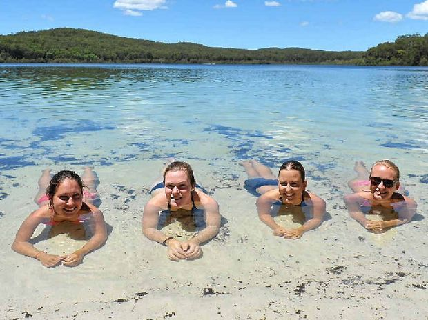 PARADISE: German tourists relax in the pristine waters of Lake McKenzie.