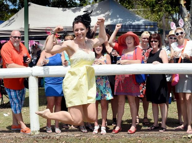 Kylie Brassell-Dellow wins the open foot race and a weekend away as her Sullivan Nicolaides Pathology workmates egg her on at the Torbanlea Picnic Races.