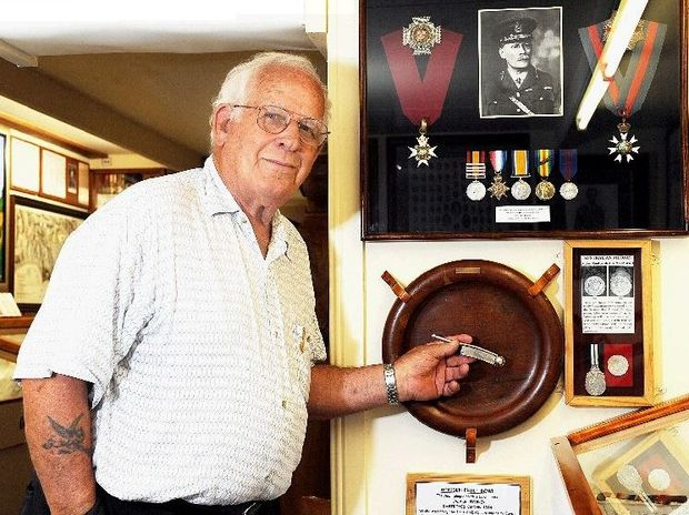 Allan Woodward with a HMAS Sydney bosun's whistle. Allan is holding the whistle against a fruit bowl from the HMAS Sydney.