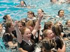 Kate Fisher (with arms extended) celebrates with fellow Year 12 girls.