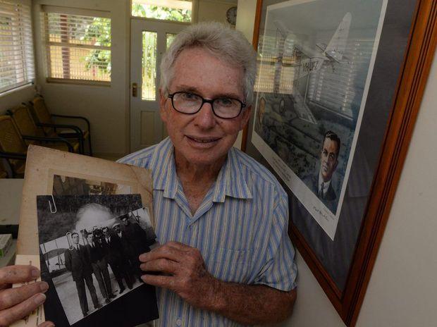 BERT HINKLER: Lex Rowland holding a photograph showing Bert Hinkler (centre) and his mechanic (far right). Photo: Mike Knott / NewsMail