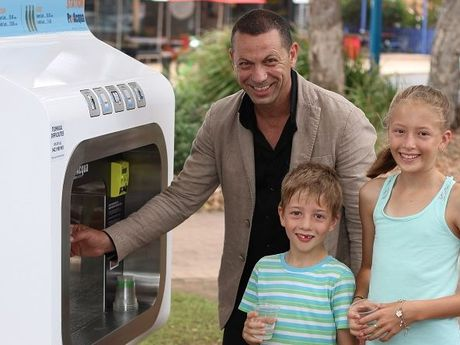 ProAqua operations manager Joe Fontana pours a cool drink from the new ProAqua water machine in Urangan for Ryan, 7, and Ellie Alder, 11, who are visiting from Gympie.