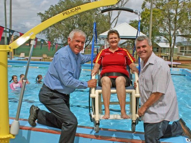 Rosewood and District Community Bank's Eirys Heit tries out the new disability hoist at the Rosewood Aquatic Centre with the help of New Hope Colliery executive general manager mining Jim Randell (left) and Ipswich City Cr David Pahlke.