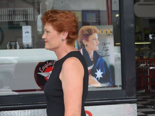 "Pauline Hanson on the street in Laidley near a poster of her campaign logo of ""Never Give Up""."