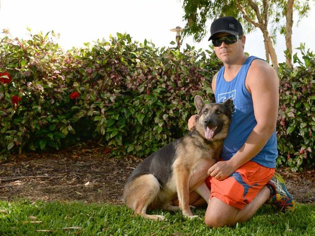 LOYAL COMPANION: Julian Lawton with Mishka who bit a bank robber as he tried to steal a bicycle over the back fence on Thursday.