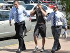 Detectives lead the accused man into the Mackay police station.