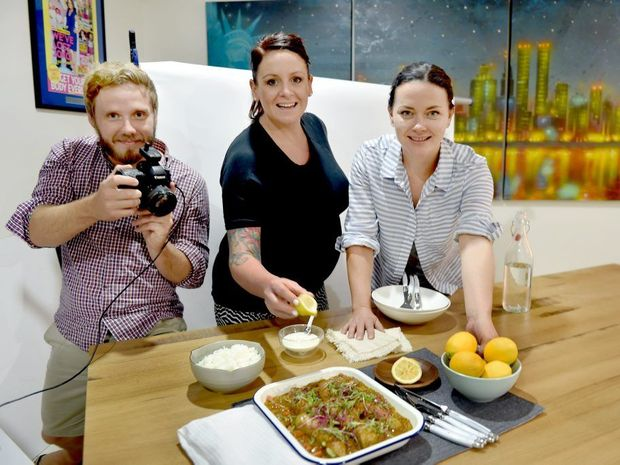 Photographer Glen Wilson, Steph Mulheron and food stylist Krista Graham with a sausage curry being photographed for Eat Meat Sweet.