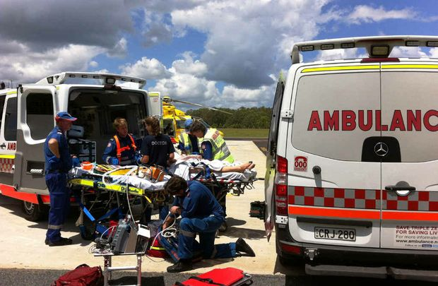 URGENT WORK: Paramedics and Westpac Chopper crew prepare the woman for the flight to hospital. Photo: Contributed