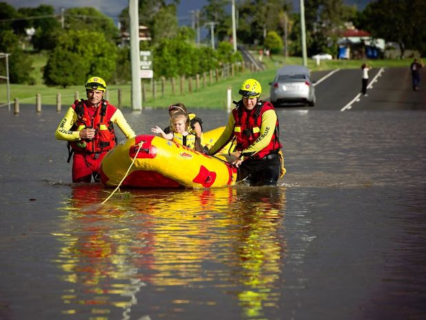 A swift water rescue team took a boat across the 60-metre section of flooded road and picked up the two young girls, bringing them back to safety.