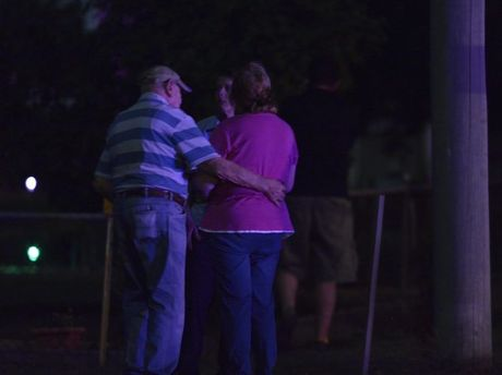 People gather outside the home where three people were shot dead.