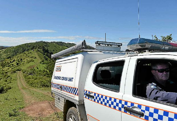 CRASH SCENE: A police Forensic Crash Unit vehicle makes its hazardous way from the almost inaccessible crash site near Woolooga yesterday