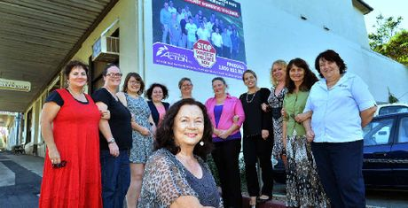 MESSAGE HITS THE STREETS: Community Action Erin House manager Bernadette Wright with colleagues and the newly installed billboard on the side of Power and Cartwright Solicitors in Mary St yesterday.