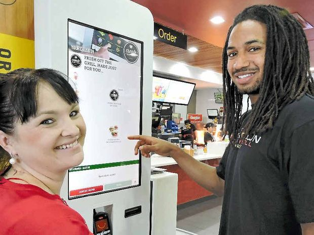NEW OPTIONS: McDonald's Northern Beaches and Caneland Central owner Niki Ramsay shows the Create Your Taste menu to Mackay Meteors player Mathew Adekponya.