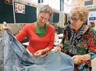 Melissa Larsen and Kathryn Woodruff wearing their upcycled necklace and scarf respectively and taking a look at a pinafore being crafted from pairs of jeans.