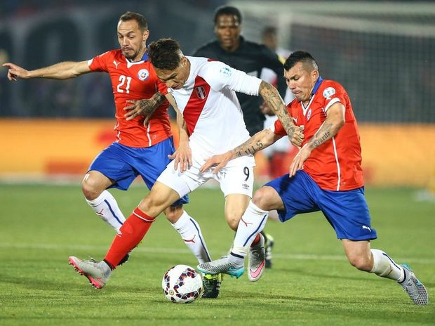 Chile's Marcelo Diaz, left, and Gary Medel, right, challenge Peru's Jose Guerrero, center, during the Copa America 2015 semi-final soccer match between Chile and Peru at the National Stadium in Santiago, Chile, 29 June 2015. Chile qualified for the Copa America final on Monday (29 June 2015) after two goals from Eduardo Vargas gave them a 2-1 win over Peru in an action-packed semi-final marked by another controversial refereeing decision. Peru had to play with 10 men for most of the match after Carlos Zambrano, who was yellow carded in the seventh minute, was harshly sent off for a high challenge 13 minutes later. Chile got the opener on 42 minutes when Vargas managed to poke the ball home from three yards after an Alexis Sanchez cross had come back off the post. Television replays showed him to be marginally offside. Peru equalised on the hour mark when Paolo Guerrero split the Chilean defence with a pass for Luis Advincula and his vicious cross was turned into his own net by Gary Medel. Peru's lead lasted just four minutes, though, and again it was Vargas who got Chile's goal, lashing home an unstoppable strike from 30 yards.