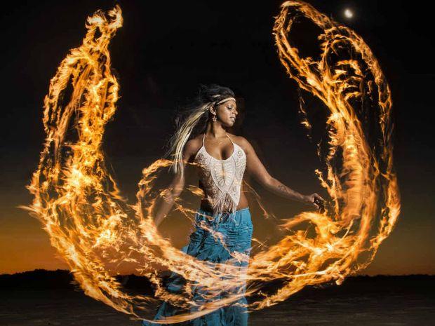 Mallika Van Pelt shows off her fire-twirling skills on Turners Beach in Yamba.