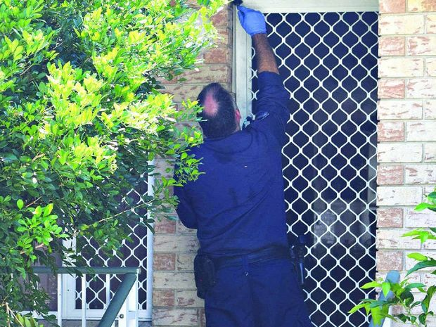 LOOKING FOR CLUES: A police officer dusts a Caloundra unit for fingerprints while investigating a suspected arson.