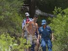 Injured climber Kieran Smith makes his way down Table Top Mountain assisted by Queensland Ambulance Service paramedics.