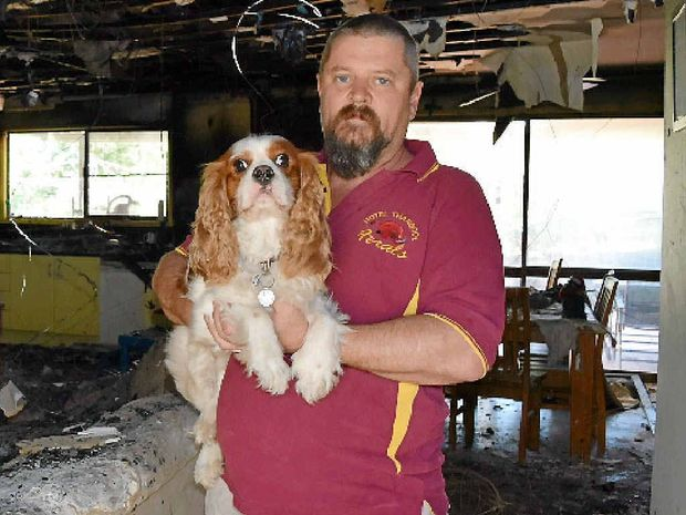 Darren Maddox holds family dog Ollie after a house fire tore through his Thangool property.