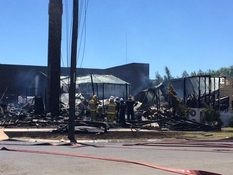 Firefighters search through the rubble of the Tattersalls Club Hotel in Pittsworth, destroyed by fire overnight.