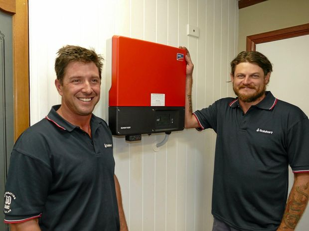 POWERED UP: Grafton Electrical electrician Jimmy Dawson, right, will be the beneficiary of a grant that will help train him to install the new Tesla powerwall batteries that promise to revolutionise the domestic use of renewable energy. Jeff Walters, the son of business owner Ian Walters, will also be trained later should demand for the product warrant it.