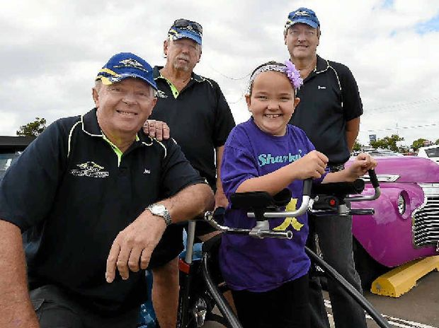 Wide Bay Rodders members Jeff Neels, Des Batten and Graham Farley donated $7000 on behalf of the club to help Sharky Lowrie learn to walk.