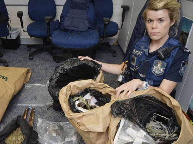 DRUG RAID: Constable Jasmin McCabe with marijuana allegedly found at a Goodna address.