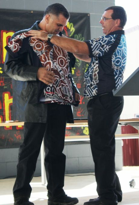 Former principal Chris Sarra being presented with a Cherbourg State School staff shirt by principal Peter Sansby.