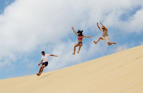 JUMPING FOR JOY: Urangan's Joe Sutherland won the I AM Summer prize, a Nikon D3300 camera kit thanks to this stunning holiday shot of his family jumping dunes at Fraser Island.