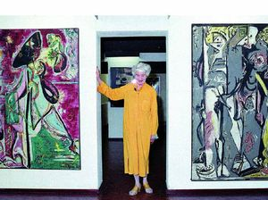 American art collector Peggy Guggenheim poses between early paintings by Jackson Pollock.