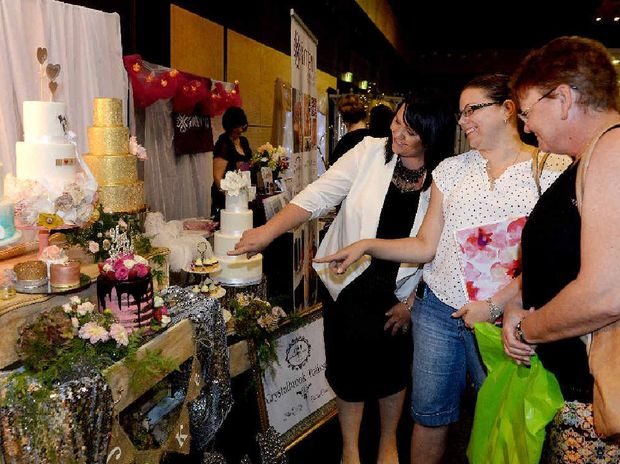 CAKE ART: Jodi Dillon of Crystalbrook Patisserie shows bride-to be Kylie Streeter and Wendy Streeter some of her cakes at Mackay's 30th Premier Bridal Fair.