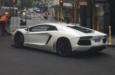 A black Mercedes-Benz rolled into a parked Lamborghini Aventador on Auckland's High St, apparently after the Mercedes driver struggled to reach for a parking machine. Photo / Supplied