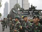 Indonesian soldiers stand guard near the site where an explosion went off in Jakarta, Indonesia Thursday, Jan. 14, 2016. Attackers set off explosions at a Starbucks cafe in a bustling shopping area of downtown Jakarta and waged gun-battles with police Thursday, leaving bodies in the streets as office workers watched in terror from high-rise windows. (AP Photo/Dita Alangkara)