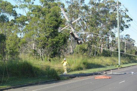 CRASH: An electricty worker inspects damage to powerlines on Telegraph Rd after a crash there this morning. Photo Craig Warhurst / NewsMail