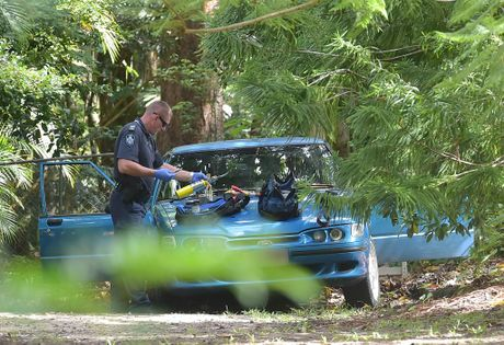 A police forensics officer inspects a yellow gas torch seized at a Thompson Rd property near where a Strawberry Rd home was destroyed in a suspected arson.