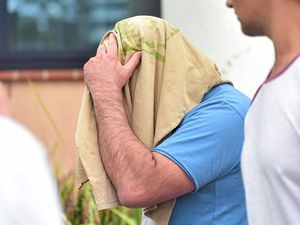 Glenn Brian Tidyman, 43, (with face covered) leaves Maroochydore Watch House after being granted bail on charges of common assault and entering a dwelling with intent by break at night using violence.