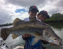 Ethan helps his younger brother Nate hold up a barramundi caught in the Boyne River.
