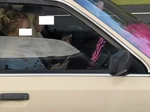 SNAPPED: The driver was photographed checking out her phone and not wearing a seatbelt in wet conditions on the Bruce Highway on Sunday.