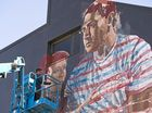 Fintan Magee paints on the SES building wall in Hume St car park for First Coat, Monday, May 30, 2016.