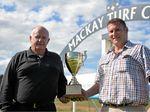 Mackay Turf Club chairman Lou Kinsey, who has a horse running today, with committee member Ryan Van de Velde, holding the Mackay Cup.