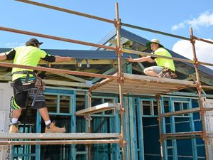 ON TRACK: Carpenters Izac Browning and Gavin Mead work hard with the team so Gatton's new hotel can open in December.