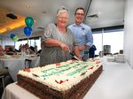 Diana Abraham, with help from Chris Watt, cutting the cake at the Meals on Wheels 30th birthday.