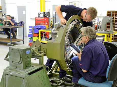 Aircraft technician Chris Smith (standing) and team leader Ross Gibbon work on an Abrams turbine.