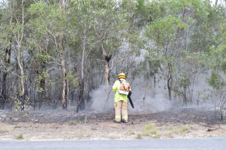 SUSPICIOUS: Torquay Fire Station Officer John Pappas puts out the last flames at a scrub fire on Walkers Rd, Urangan.