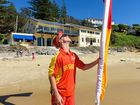 Lifeguard Will Brighton puts up the flags for the start of the surf season at Yamba Main Beach.