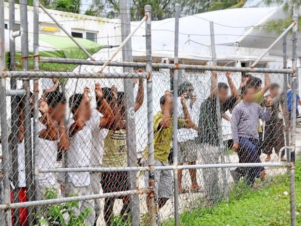 A March 21, 2014 file image of Asylum seekers staring at media from behind a fence at the Oscar compound in the Manus Island detention centre, Papua New Guinea. PNG Prime Minister Peter O'Neill says the Manus Island detention centre will close following a decision by the PNG Supreme Court that declared it to be unconstitutional, Wednesday, April 27, 2016. (AAP Image/Eoin Blackwell) NO ARCHIVING