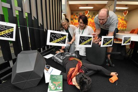 """Jane Mackin and Kim Shelton from USC library and Mark Shelton from the council library at the scene of a """"murder"""" for people to solve."""
